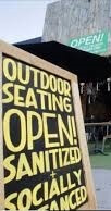 "Chalkboard reading ""outdoor seating open, sanitized, socially distanced"""