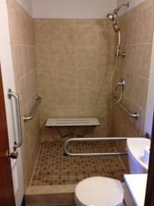 Bathroom equipped with grab bars and safety railings.