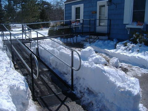 L-shaped modular wheelchair ramp at front entrance to home after heavy snowstorm.