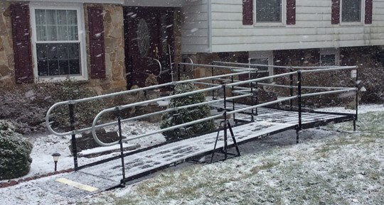 L-shaped modular wheelchair ramp at front entrance of a home during snowstorm