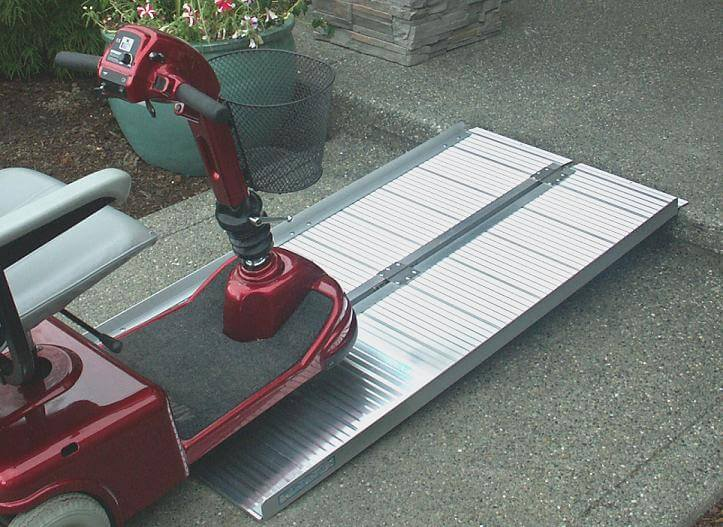 Portable aluminum ramp folds open to provide access for red scooter